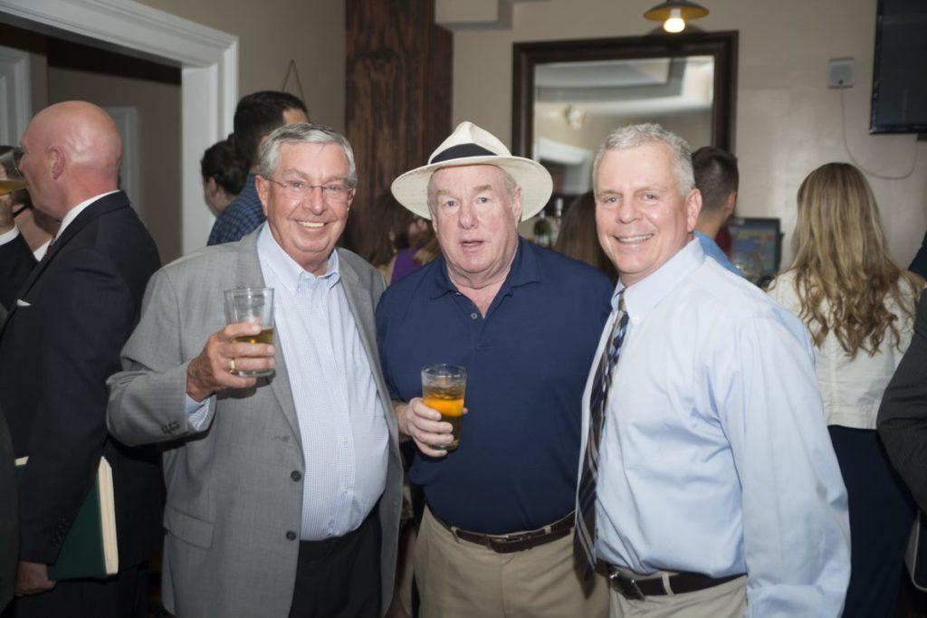 3 Men holding rinks smiling for camera